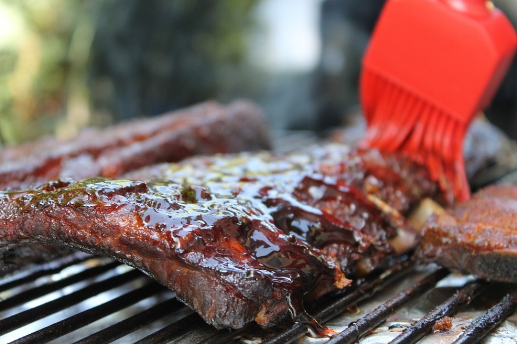 Best BBQ in Kansas City - ribs on a grill being brushed with sauce