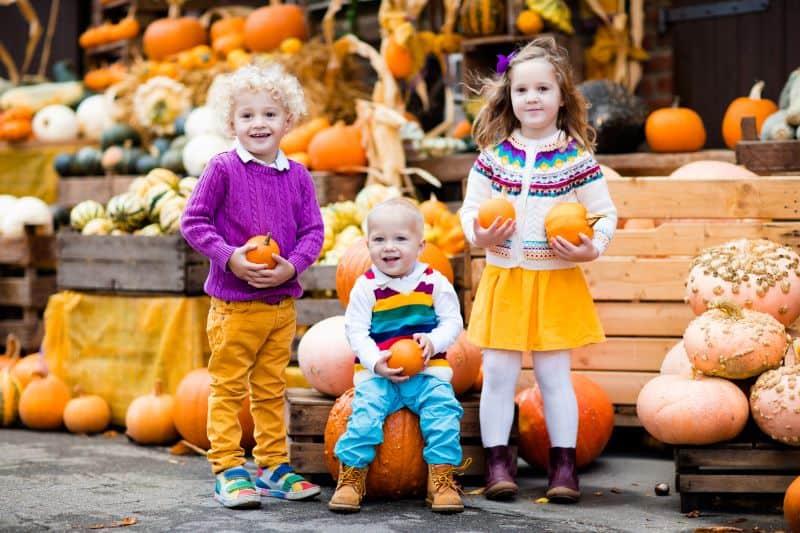 Kansas City fall festivals - three young kids holding pumpkins