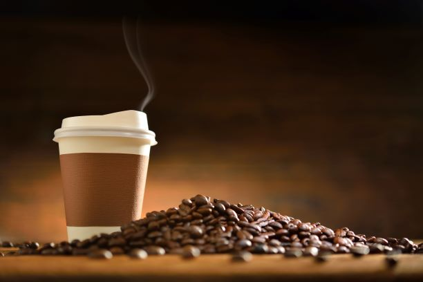 National Coffee Day - coffee in a paper to-go cup with a pile of coffee beans