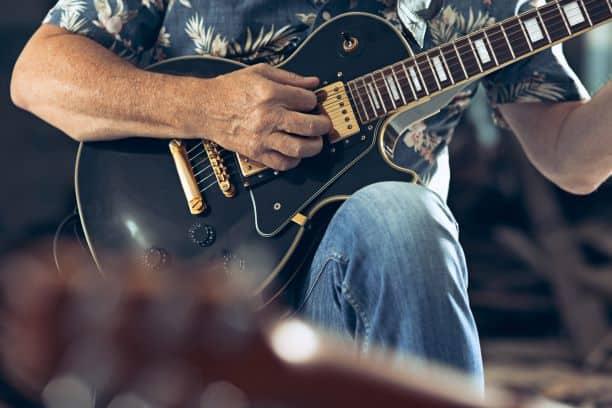 Knuckleheads Open Jam - man's finger strumming a guitar