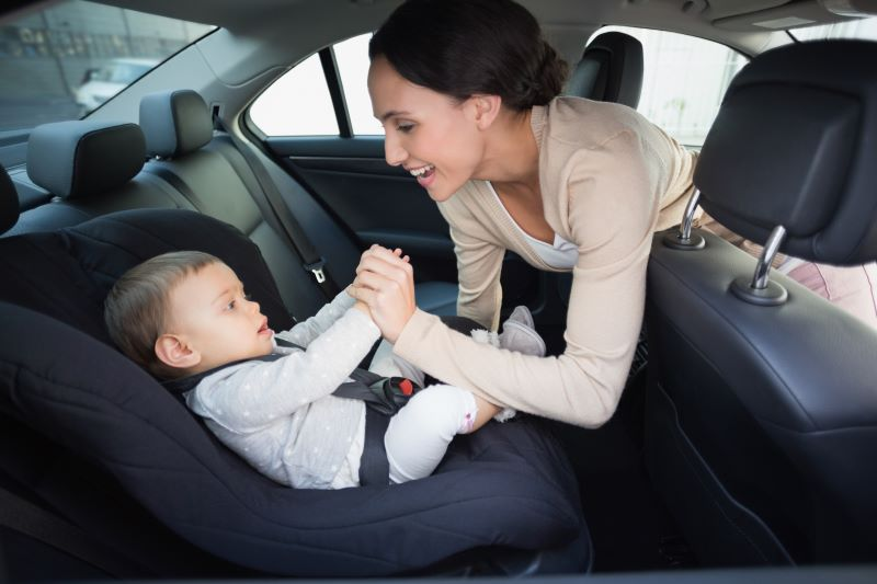 Target car seat trade-in event - mother putting infant in car seat