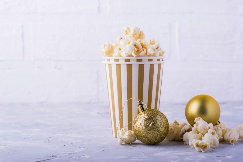 Classic Holiday Movies - box of popcorn with gold Christmas ornament balls