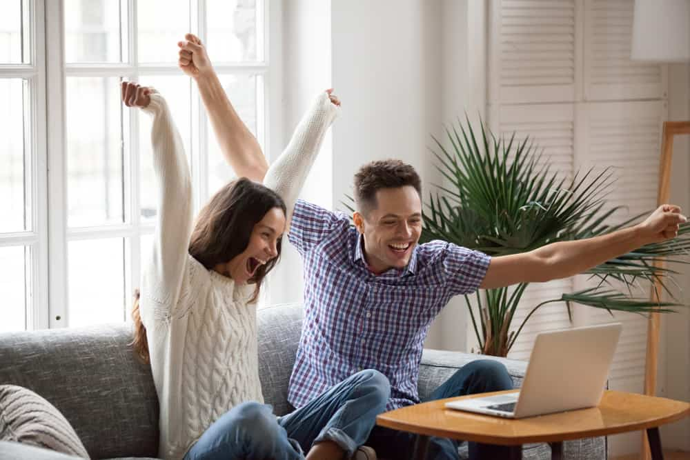 young couple cheering in front of a laptop